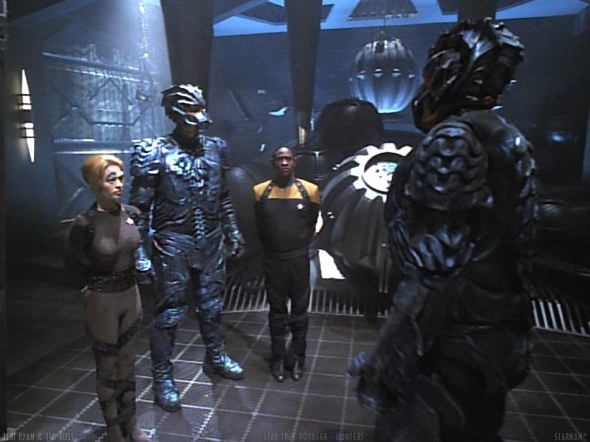 An Alpha (right) and Beta Hirogen with two Prey, Tuvok and Seven of Nine.
